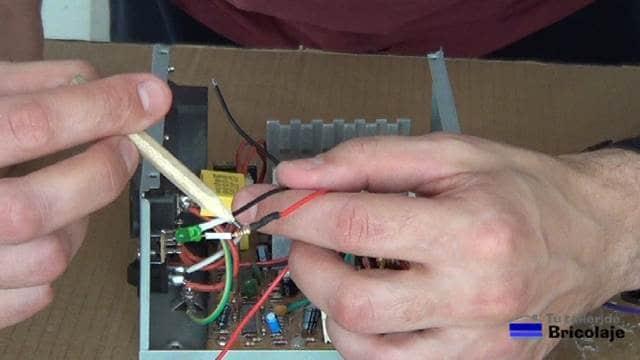 soldando una resistencia al led indicador de funcionamiento de la fuente de alimentación de laboratorio casera