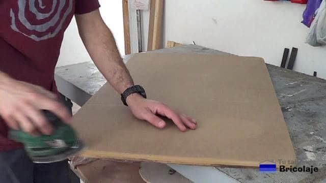lijando los cantos de la cubierta de la mesa