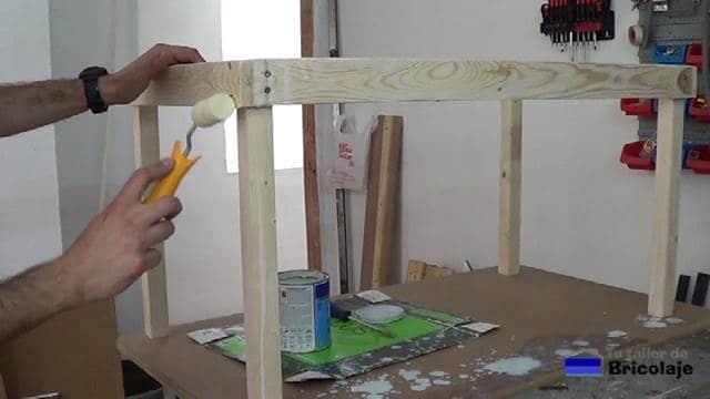 aplicando el tapaporos a la madera de la mesa para niños con tornillos