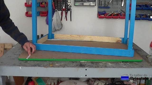 centrando el tablero sobre la estructura o esqueleto de la mesa para niños con tornillos