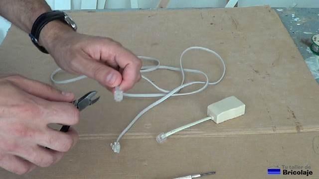 cortando una de las puntas del cable de teléfono