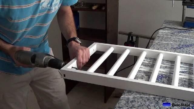 taladrando los laterales de la reja para sujetarla a la pared