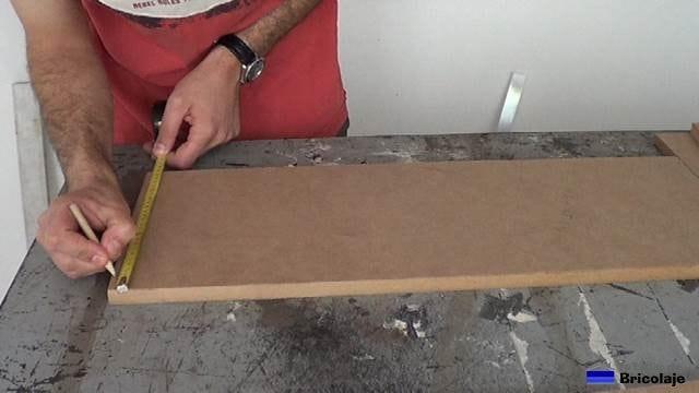 midiendo el lugar donde colocar los tornillos para montar la estructura
