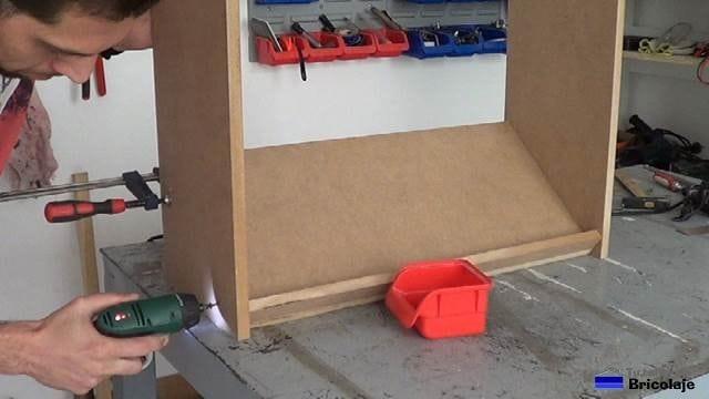 sujetando la balda a la estructura de la zapatera mediante tornillos