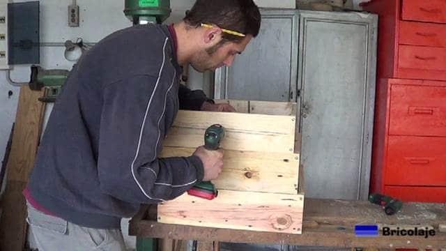 taladrando para sujetar las partes para formar la jardinera escalonada de madera de palets