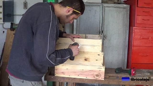 sujetando con tornillos para formar la jardinera escalonada de madera de palets