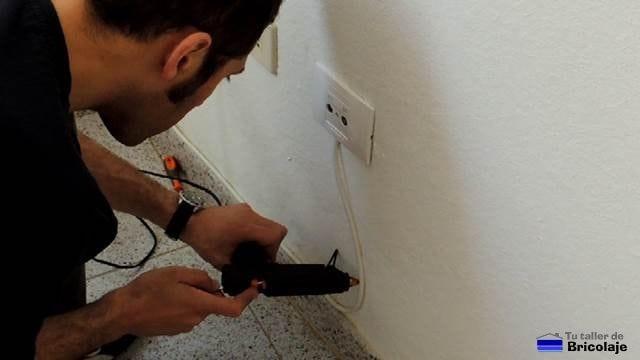 colocando el cable de televisión con silicona caliente