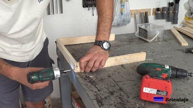 atornillando las madera de palet que formarán las patas inferiores