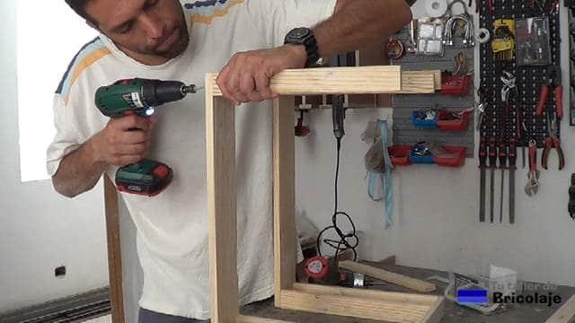 atornillando la estructura de la parte superior de la mesa auxiliar