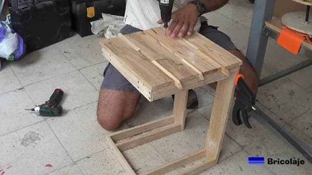 montando la cubierta superior de la mesa auxiliar de terraza
