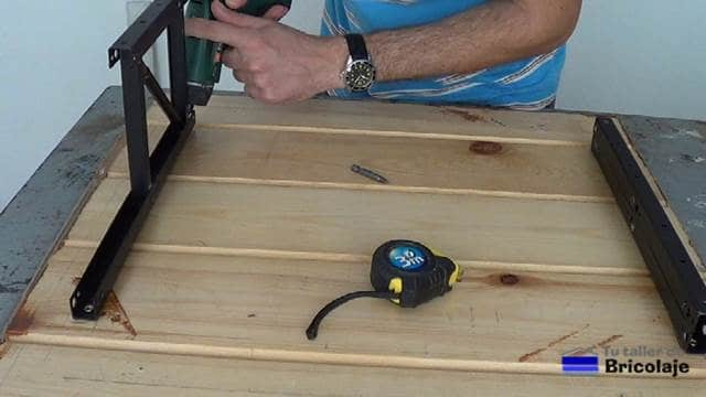 colocando los tornillos para sujetar el sistema de elevación de mesas