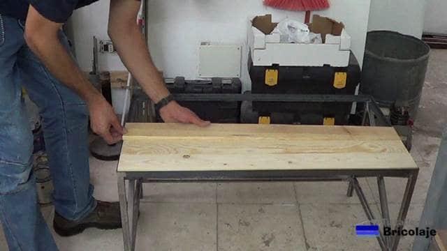 colocando la madera de palets en la cubierta superior de la mesa de centro de hierro