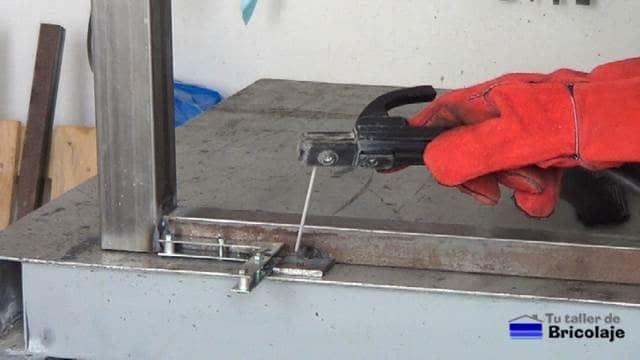 soldando el trozo de pletina con el agujero a la estructura de hierro de la mesa