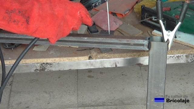 soldando la pletina con el agujero a la estructura de hierro de la mesa