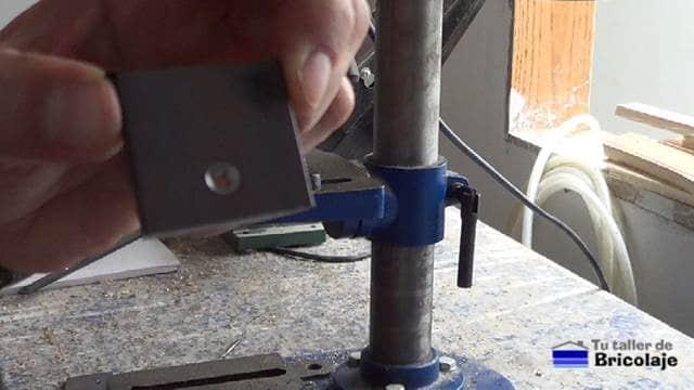 avellando un agujero en una pletina de hierro para sujetar la cubierta de madera de la mesa