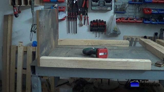 colocando las patas a la base de la mesa recibidor de madera de palets