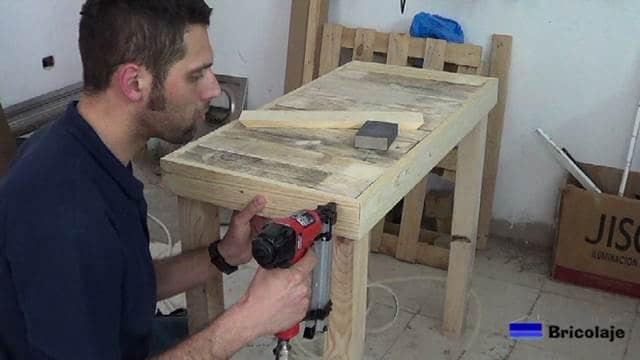 clavando las madera necesarias para realizar la mesa recibidor