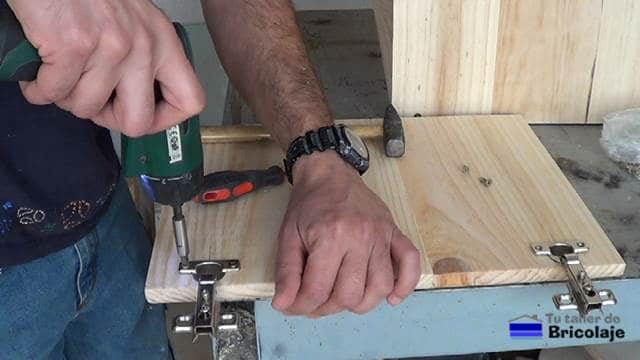 atornillando las bisagras de cazoleta a las puertas del mueble auxiliar para el baño