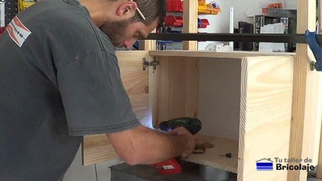 perforando para sujetar las patas al mueble auxiliar