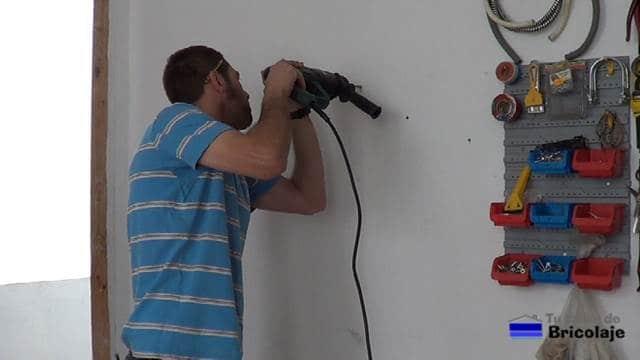 abriendo los agujeros en la pared para colocar el organizador de taladros y sus accesorios