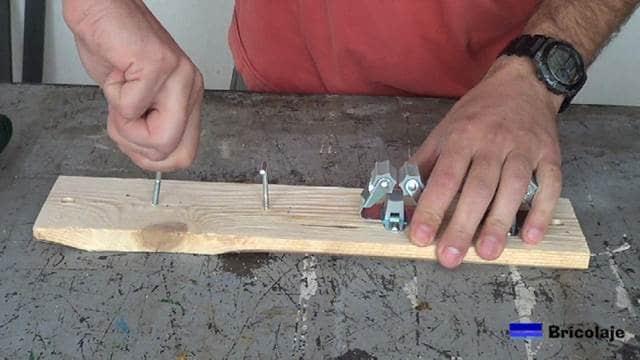 enroscando las alcayatas en la base de madera