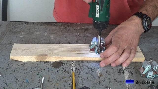atornillando los soporte a la base de madera del organizador