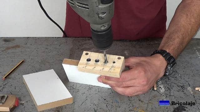 abriendo el agujero en el grosor de la madera con la plantilla