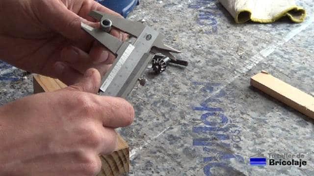 tomando la medida exterior del casquillo metálico para perforar la madera para insertarlo