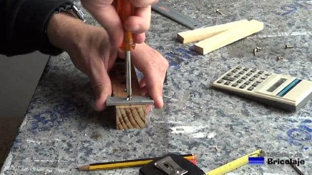 atornillando la pletina sobre la base para unir madera mediante espigas o tarugos