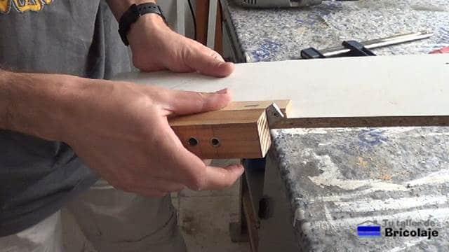 colocando la guía sobre el trozo de aglomerado plastificado en blanco de 16 mm de grosor