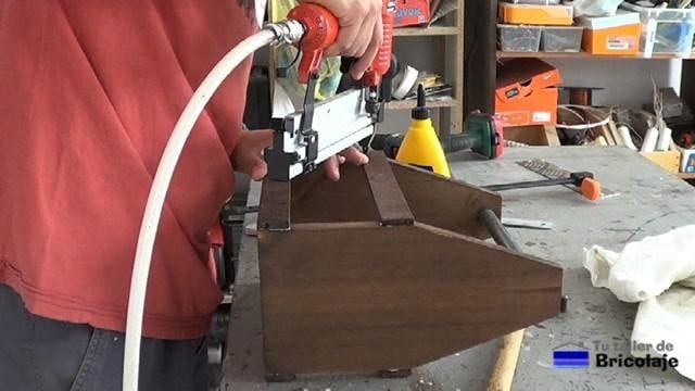 sujetando las distintas partes que forman el porta cervezas con tachas o clavos