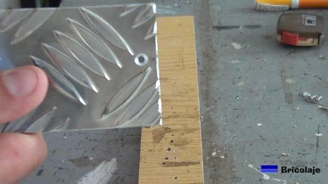 abriendo agujeros a la chapa de aluminio para sujetarla al porta cervezas