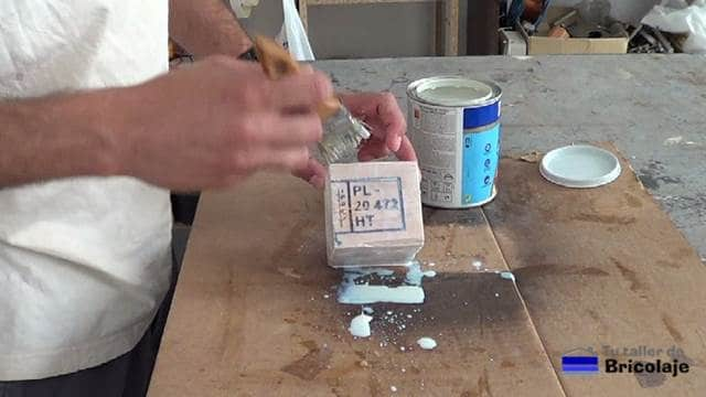 aplicando tapaporos al agua al portalápices o lapicero de madera