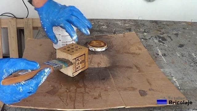 aplicando un barniz tinte en color cerezo al portalápices o lapicero de madera de palets