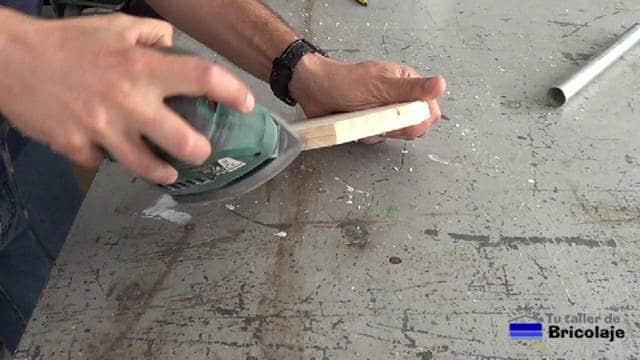 lijando la madera de la base del portarollos