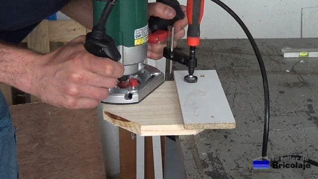 rebajando los cantos de la madera de la base con la fresadora