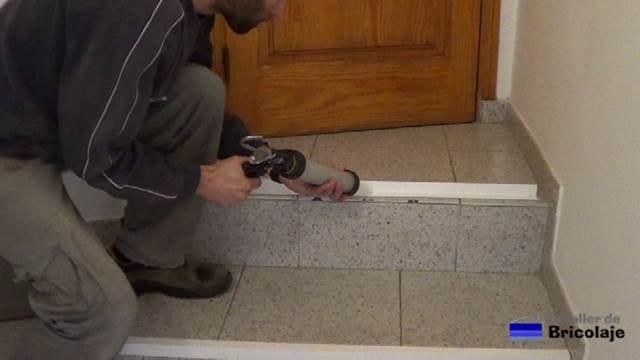 aplicando adhesivo de montaje para pegar el ángulo al suelo