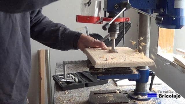 abriendo los agujeros en la cubierta de madera del aplique de pared