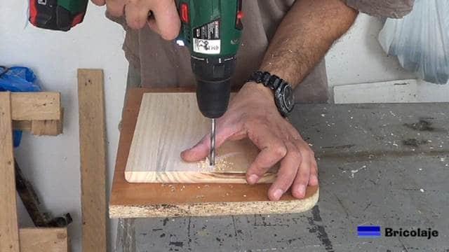 abriendo los agujeros en la madera para sujetarla al soporte de pared