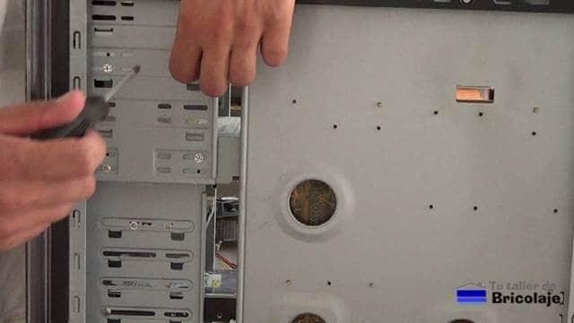 retirando los tornillos para extraer las unidades ópticas, el disco duro y la disquetera