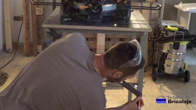 marcando el agujero en la pletina para poder sujetarla a la estructura de la mesa