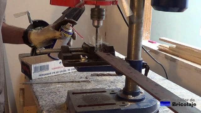 abriendo el agujero a la pletina para poder sujetarla a la estructura de la mesa
