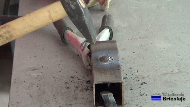 retirando la escoria generada por la soldadura de arco
