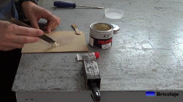 preparando la masilla de fibra de vidrio para tapar o rellenar el agujero en el hierro o metal