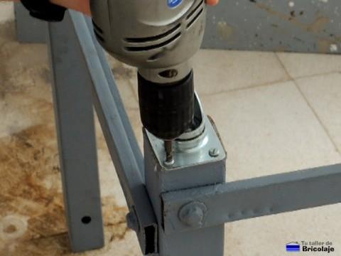 atornillando las ruedas a las patas con ayuda del atornillador eléctrico