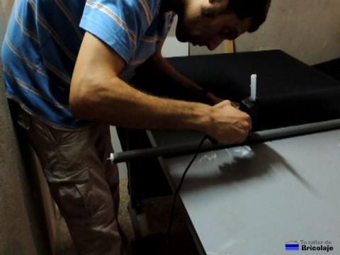 aplicando silicona caliente para pegar el estor al tubo superior de fijación