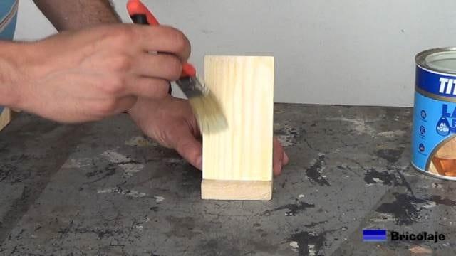 aplicando tapaporos a la madera que forma el soporte para el smartphone