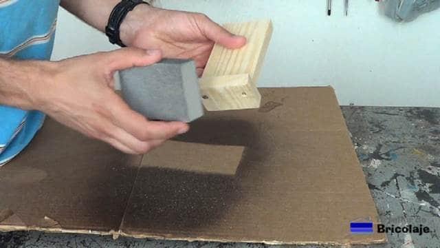 lijando la madera que forma el soporte para el smartphone
