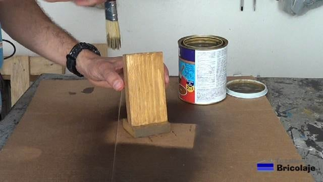 aplicando el barniz tinte al soporte para el smartphone