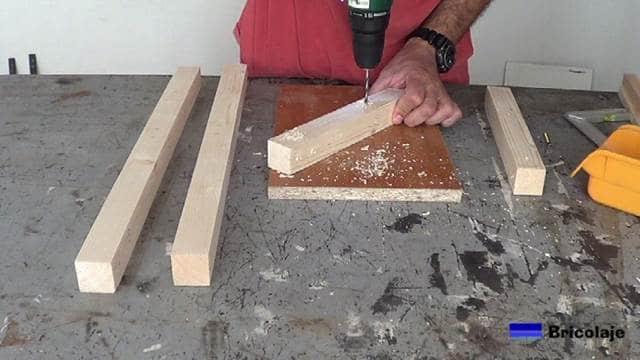 perforando las marcas realizadas para hacer la silla de madera para niños con tornillos